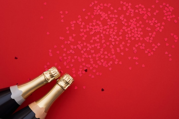 Champagne-flessen met confettienharten op rode achtergrond. ruimte kopiëren, bovenaanzicht