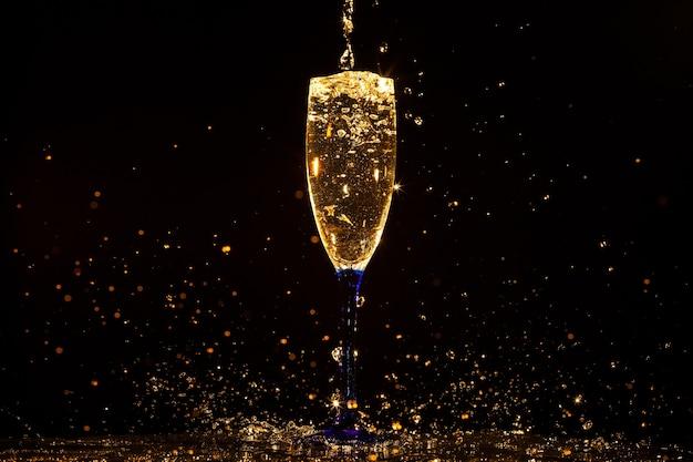 Champagne gieten in glas op zwart