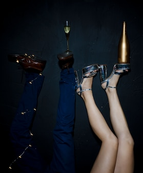 Champagne glas en fles op vrouw en man voeten