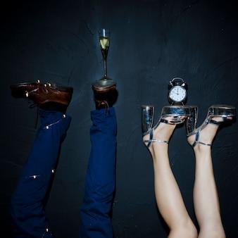 Champagne glas en klok op vrouw en man voeten
