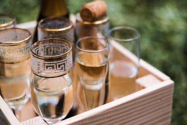 Champagne-glazen in houten krat bij in openlucht Gratis Foto