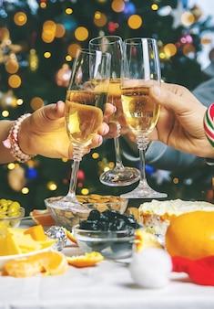 Champagne in de hand tegen de achtergrond van de kerstboom. mensen. selectieve aandacht. vakantie.