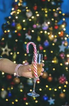 Champagne in de hand tegen de achtergrond van de kerstboom. selectieve aandacht. vakantie.