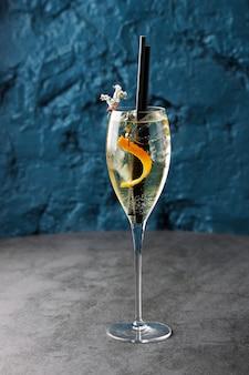 Champagne in een glas met sinaasappelschil en twee tubes