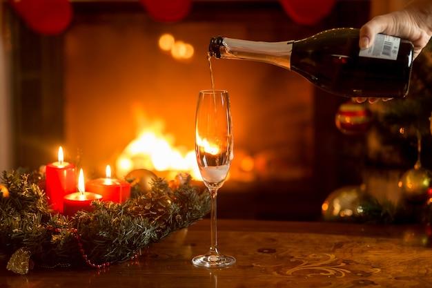 Champagne in glas gieten op tafel versierd voor kerstmis