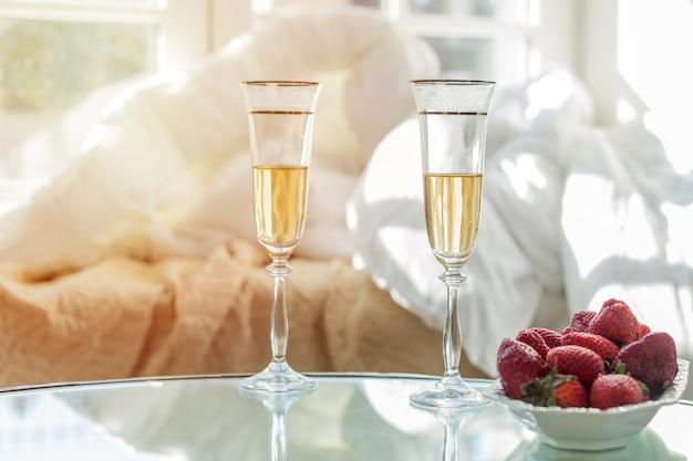 Champagne in glazen en aardbeien op een witte plaat