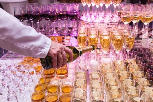 Champagne in mooie glazen gieten. barman die champagne in glazen giet