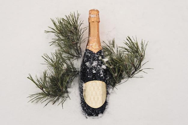 Champagne, kerstdecor over sneeuw en dennenboom met kopieerruimte. de viering van nieuwjaar en kerstmis op straat in de winter.