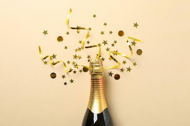 Champagnefles en glitter op beige, ruimte voor tekst