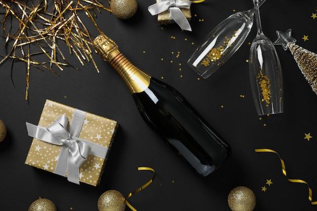 Champagnefles, glazen en kerstballen op zwart, bovenaanzicht
