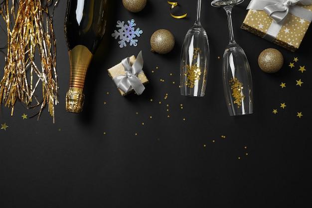 Champagnefles, glazen en kerstballen op zwart, kopie ruimte