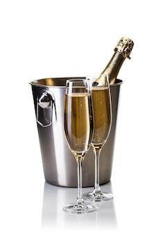 Champagnefles in emmer met glazen champagne op wit wordt geïsoleerd