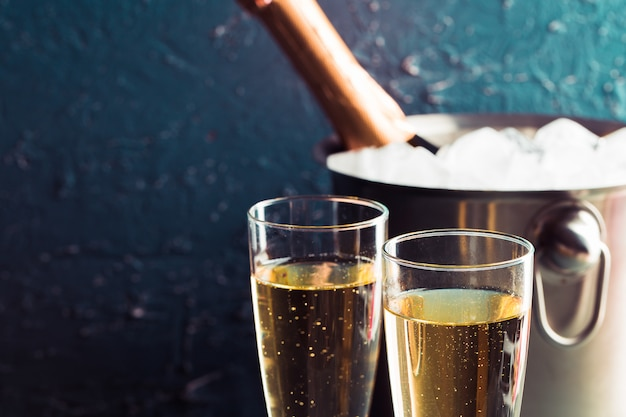 Champagnefles in emmer met ijs en glazen champagne