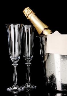 Champagnefles in emmer met ijs en glazen op zwart