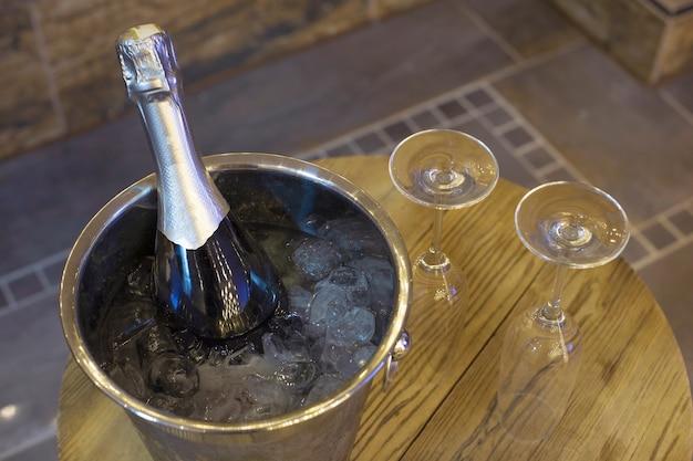 Champagnefles in koelere emmer met ijs en twee champagneglazen op houten tafel romantisch