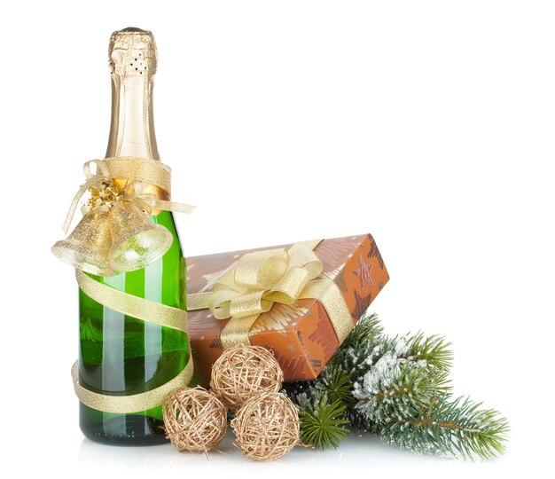 Champagnefles, kerstcadeau en besneeuwde spar. geïsoleerd op witte achtergrond