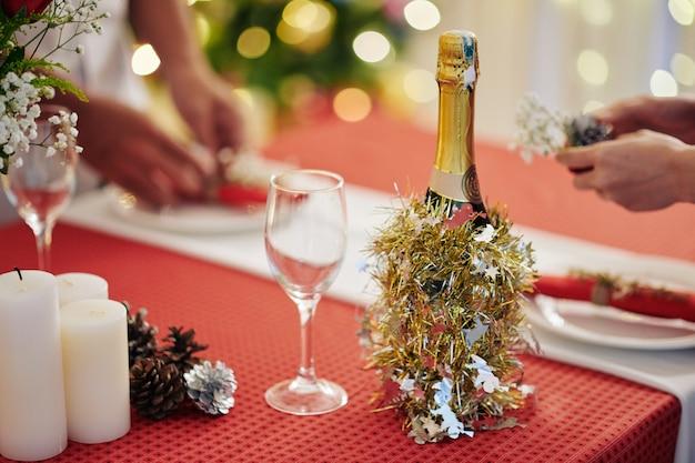 Champagnefles versierd met klatergoud op kersttafel