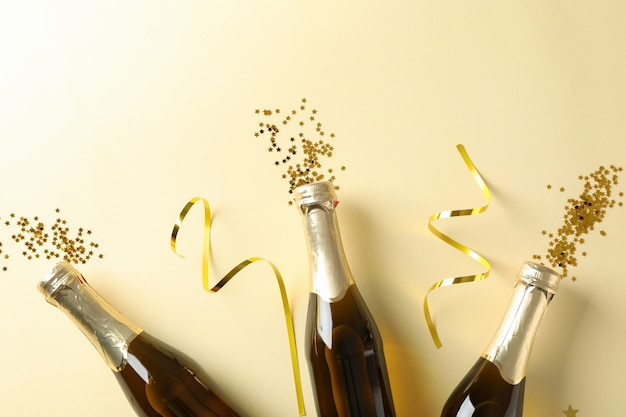 Champagneflessen en glitter op beige. concept vakantie