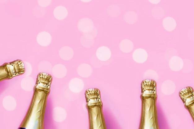 Champagneflessen op een pastel roze achtergrond met bokeh lichten