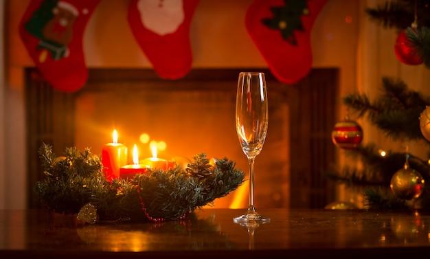 Champagnefluit op kersttafel voor brandende open haard