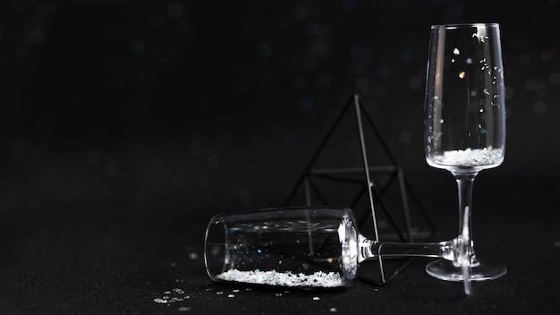 Champagnefluiten versierd met glitters in de buurt van een zwarte driehoek