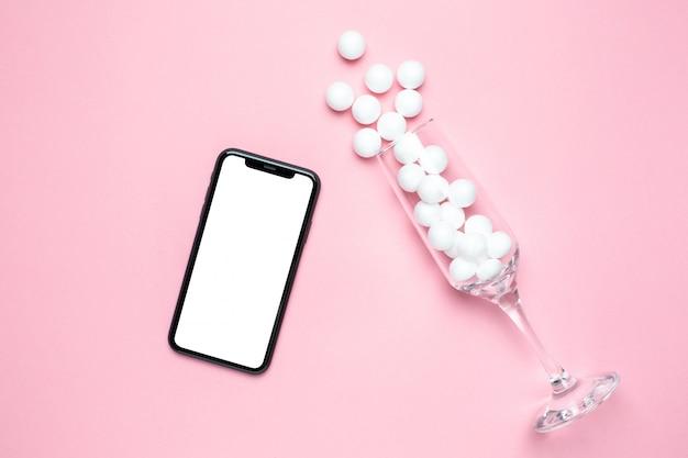 Champagneglas met witte ballen en mobiele telefoon mock up op roze minimalistische stijl.