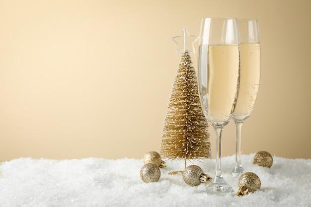 Champagneglazen en kerstballen tegen beige ruimte, ruimte voor tekst