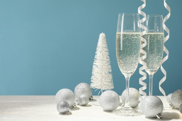Champagneglazen en kerstballen tegen blauwe ruimte, ruimte voor tekst