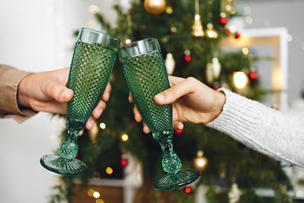 Champagneglazen in handen van mensen op de achtergrond van een wazig kerstboom. toast op feestje. kerstmis en nieuwjaar viering concept.