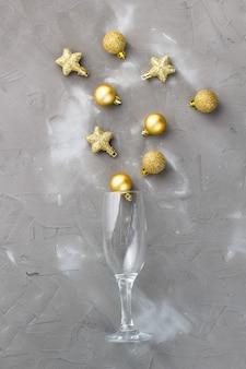 Champagneglazen met gouden ballen en sterren op grijze achtergrond, kopieer ruimte. kerstmis nieuwjaar concept. bovenaanzicht, plat gelegd