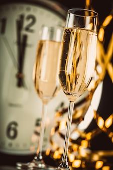 Champagneglazen met klok bijna middernacht