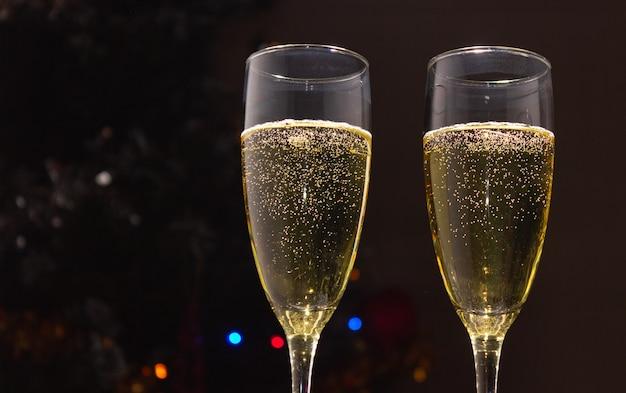 Champagneglazen op de achtergrond van een versierde kerstboom