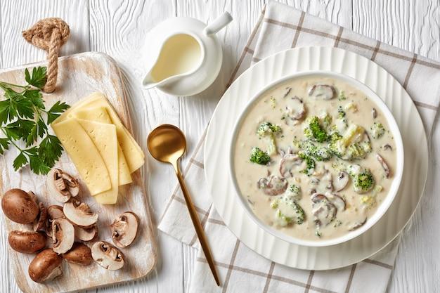 Champignon broccoli kaassoep in een witte kom met een gouden lepel en ingrediënten op een witte houten tafel, horizontale weergave van bovenaf, close-up
