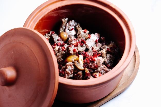 Champignon- en vleesplakken in pot gegarneerd met gedroogde berberis