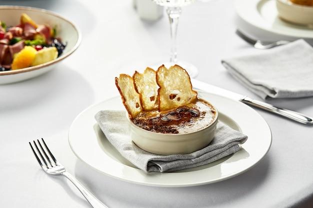 Champignon julienne met croutons op de feesttafel, champignons julienne en andere snacks op tafel met een licht tafelkleed.