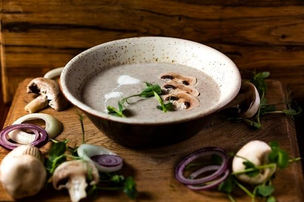 Champignonroomsoep met peterselie-selderij in een keramische plaat op een houten tafel