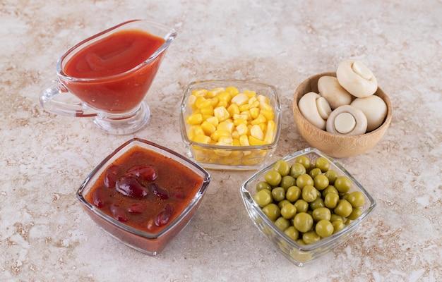 Champignons, groene erwten, maïskorrels, ketchup en rode saus op marmeren oppervlak