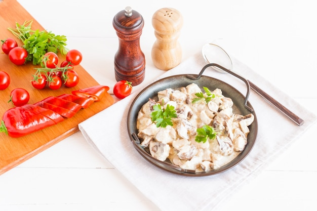 Champignons in zure roomsaus in een koekenpan op een witte achtergrond. het concept van heerlijk gezond eten.