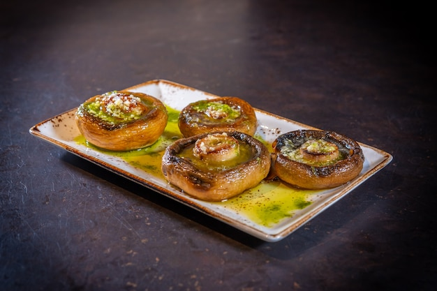 Champignons met olijfolie en knoflook op een zwarte achtergrond, op een witte plaat