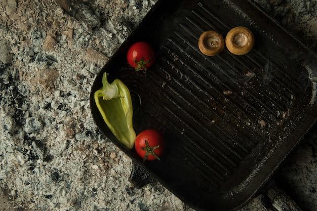 Champignons met tomaten op een bakplaat liggen op houtskool. het gerecht wordt gekookt en gerookt op houtskool