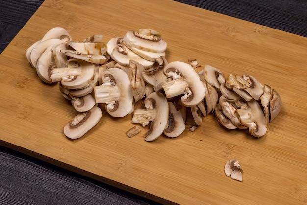 Champignons op een snijplank tijdens het schoonmaken en snijden als onderdeel van het proces van het bereiden van verse champignons voor het daaropvolgende invriezen