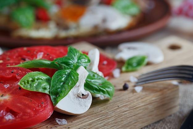 Champignons, tomaten en basilicum op rustieke houten tafel