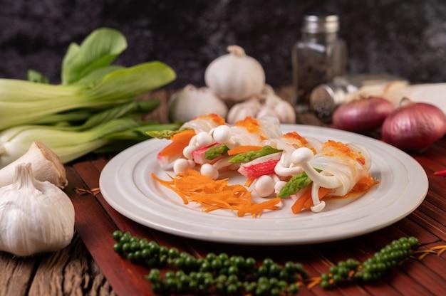 Champignons, wortelen, asperges en sla gebonden met noedels
