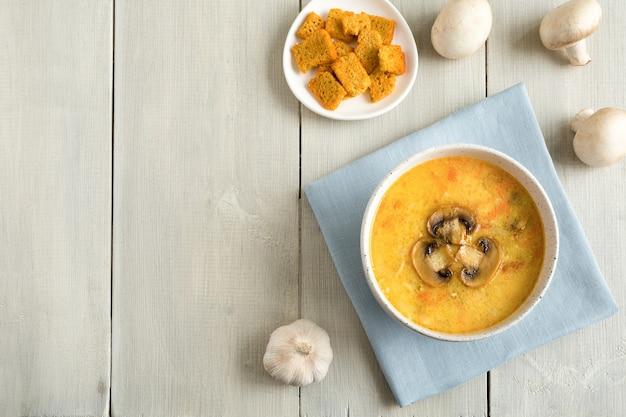 Champignonsoep in een witte kom op blauw servet. hele champignons, brood plat leggen met plaats voor tekst op een houten witte achtergrond.