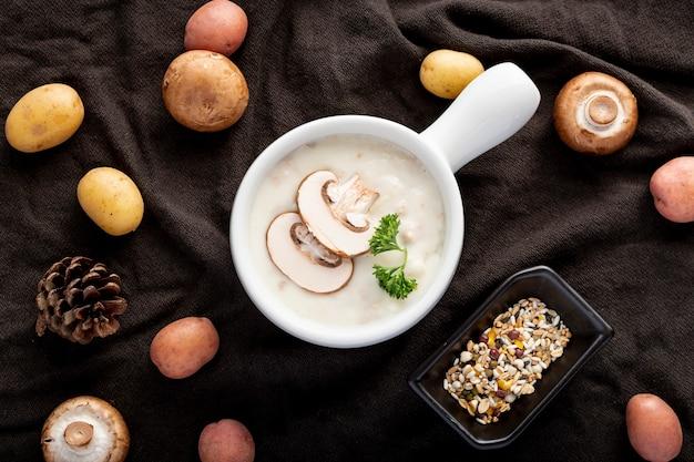 Champignonsoep in een witte pot met champignons op een zwarte doek