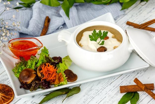 Champignonsoep in keramische portie geserveerd met salade en saus