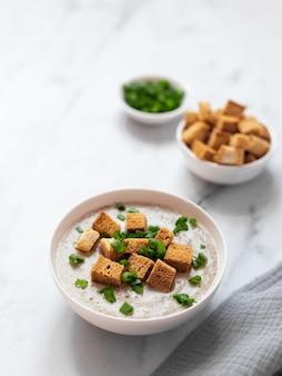 Champignonsoep-puree met ui, kaas en crackers. op een lichte achtergrond