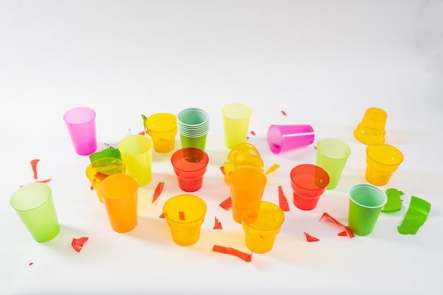 Chaotische consumptie. stelletje kleurrijke plastic bekers wordt gebroken en in onverwerkte staat gegooid