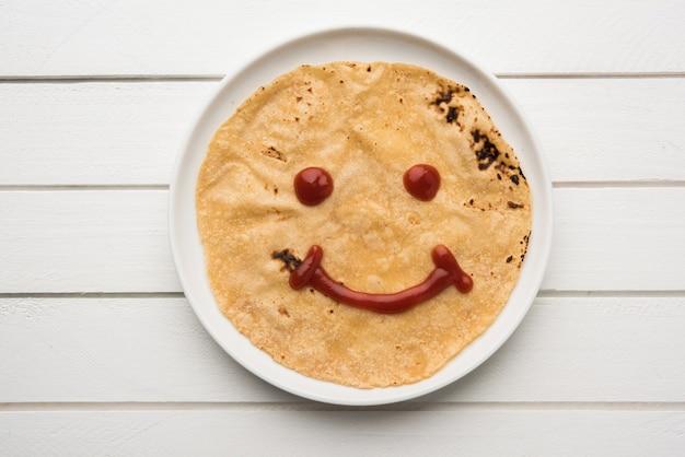 Chapati roll met tomatenketchup of fruitjam jelly met lachend gezicht, het favoriete voedselmenu van indiase kinderen voor schooltiffin-doos, selectieve focus
