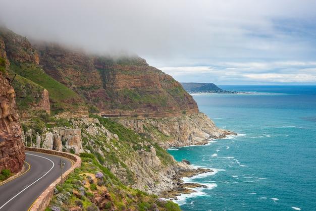 Chapman's peak drive, kaapstad, zuid-afrika. ruwe kustlijn in wintertijd, bewolkte en dramatische hemel, golvende atlantische oceaan.